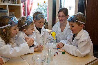 The children of the Schalchen kindergarten, (from left to right) Amelie Kogler, Dominik Junghuber, Alexander Moser and Paul Wallner investigate the properties of yeast under the watchful eye of their kindergarten teacher Maria Zauner. A balloon placed over the neck of a bottle is slowly blown up by a mixture of yeast, sugar, flour and warm water.